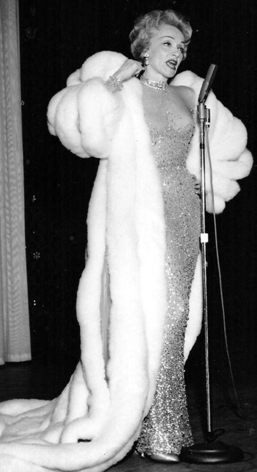Marlene Dietrich con un lungo abito da sera e pelliccia canta in tournée, anni cinquanta circa