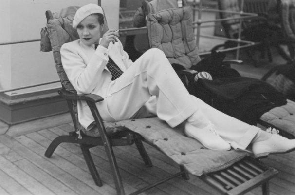 Marlene Dietrich in viaggio su un transatlantico, seduta su una sdraio indossa un completo bianco da uomo, 1933