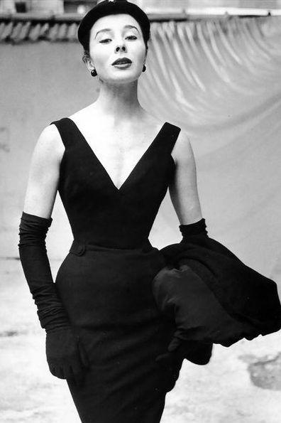 La modella indossa un abito nero di Christian Dior con profondo scollo e completato da lunghi guanti, cappello e soprabito portato su un braccio
