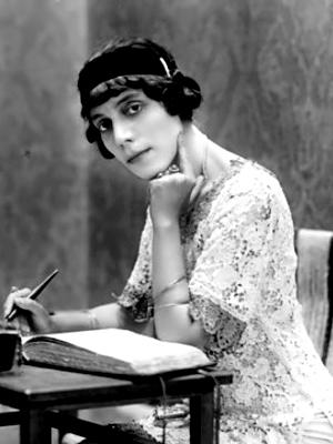 La poetessa e scrittrice Amalia Guglielminetti ritratta con una penna in mano mentre sta per scrivere su un grosso quaderno