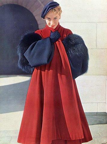La modella indossa un ampio cappotto rosso di Christian Dior con inserti di pelliccia blu navy e cappello e guanti dello stesso colore