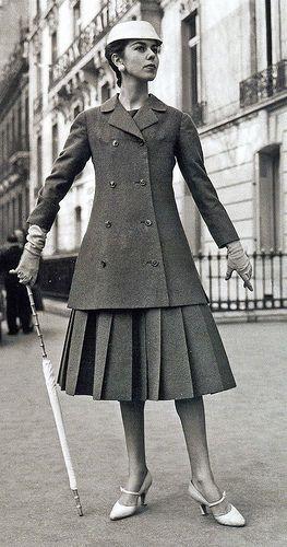 Completo formato da soprabito e gonna a pieghe completato da cappello, guanti, ombrello e scarpe. Tutto di Christian Dior, collezione 1955 linea A
