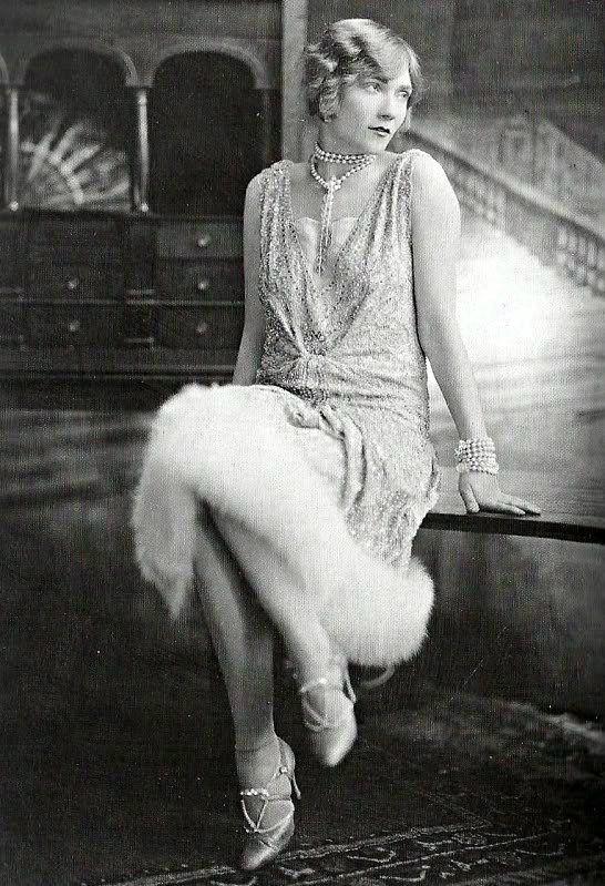 Giovane donna in abito da sera senza maniche con ricami e bordato di pelliccia con collana e bracciale di perle e scarpe col tacco