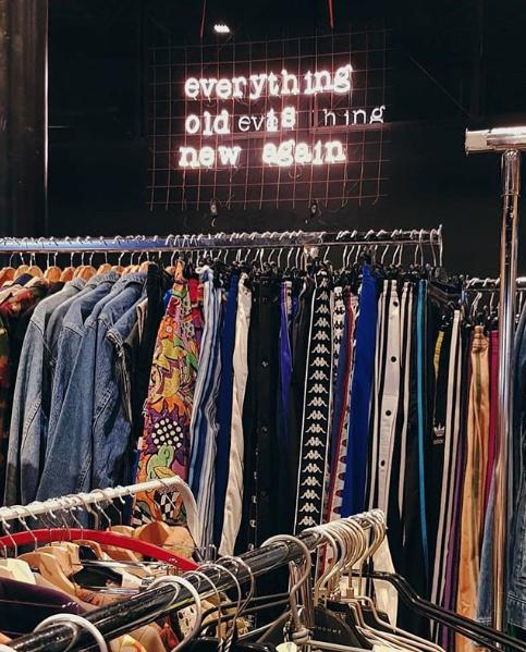Il motto di East Market scritto con le luci che illuminano uno stand di abbigliamento vintage in una precedente edizione