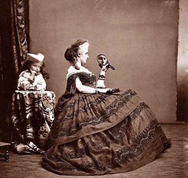 La Contessa di Castiglione si guarda allo specchio e alle sue spalle c'è il figlio Giorgio