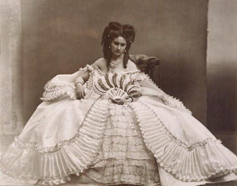 La Contessa di Castiglione seduta indossa un ampio abito bianco e regge un ventaglio di piume