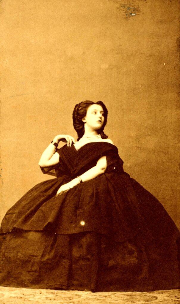 """La Contessa di Castiglione, indossa un abito scuro e grandi bracciali nella foto """"L'Interrogation"""", 1856 circa"""